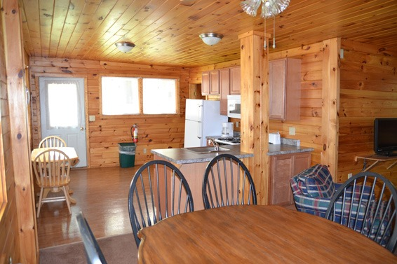 Wood paneled cabin with kitchen and dining room