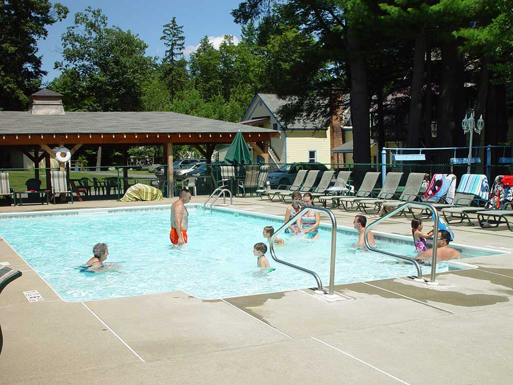 pool area with lounge chairs and swimmers