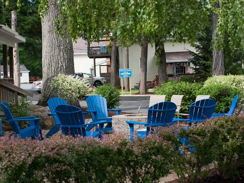 blue Adirondack chairs around stone firepit