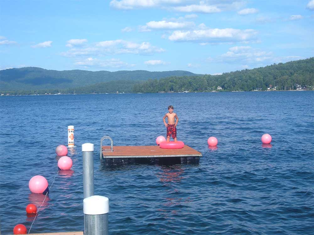 Boy on floating dock in swimming area