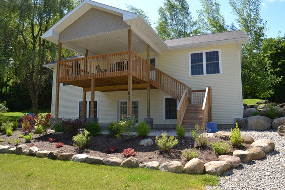 2nd floor deck with stairs leading from landscaped yard